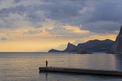 防堤的一位孤立渔夫 库存图片