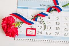 防御者2月23日-祖国天卡片的 红色康乃馨、俄国旗子和日历与被构筑的日期2月23日 免版税库存照片
