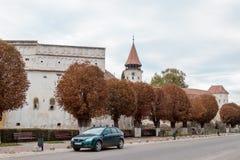 防护墙壁和城楼与被加强的教会Prejmer的时钟在Prejmer市在罗马尼亚 库存照片