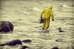 防护套服的技术员走在水中的在多岩石的海滩 库存照片