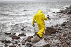 防护套服的科学家与塑胶容器走在多岩石的海滩的 免版税库存照片