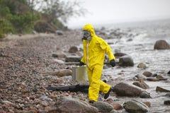 防护套服的科学家与银色案件走在多岩石的海滩的 库存图片