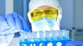 防护套服的科学家检查在试管的危险品在实验室 股票视频