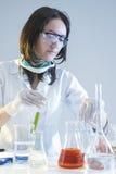 防护手套的女性实验员在与液体组分的科学实验期间在实验室 库存照片
