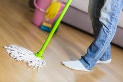 防护手套的妇女使用湿拖把,当清洗地板时 免版税库存图片