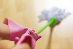 防护手套的妇女使用湿拖把,当清洗地板时 免版税库存照片