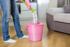 防护手套的妇女使用湿拖把,当清洗地板时 库存图片