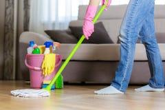 防护手套的妇女使用湿拖把,当清洗地板时 库存照片