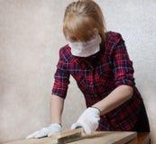 防护玻璃、面具和手套的一个女孩工作一个木板的表面上 库存照片