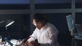 防护玻璃和白色外套的非裔美国人的电子专家与多用电表测试器一起使用和