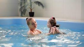 防护玻璃的逗人喜爱的白肤金发的小孩潜水在水下与他的母亲一起在游泳池尝试 股票录像