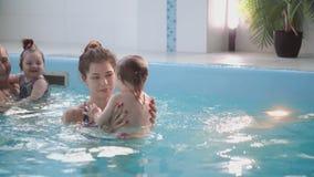 防护玻璃的逗人喜爱的白肤金发的小孩潜水在水下与他的母亲一起在游泳池尝试 股票视频