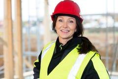 防护穿戴的确信的女性木匠在站点 免版税库存照片