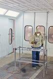 防护衣裳的人在喷漆摊工作 免版税库存照片
