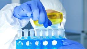 防护衣裳的科学家检查在试管的危险物在实验室 股票录像