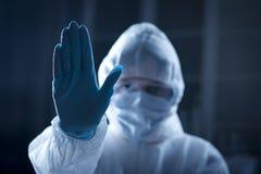 防护hazmat衣服的女性科学家用被举的手 免版税库存照片