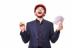 防护hemlet的激动的年轻英俊的人矿工与bitcoin在一只手上和在白色backgro在其他上隔绝的现金美元 库存照片