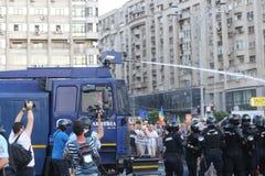 防暴警察部署高压水炮反对抗议的人群 免版税库存照片