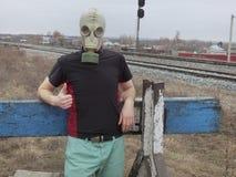防毒面具的人在铁路的死角 指向手指所有很好是 免版税图库摄影