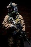 防毒面具的战士有步枪的在手上 免版税库存照片