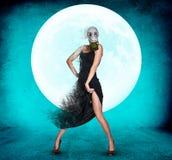 防毒面具的时髦的少妇在满月背景 免版税库存照片