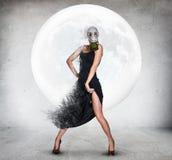 防毒面具的时髦的少妇在满月背景 免版税图库摄影