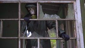 防毒面具的疯狂的潜随猎物者疯子从一个被破坏的房子看并且要攻击 影视素材