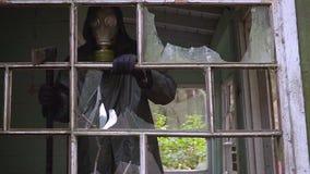 防毒面具的疯狂的潜随猎物者疯子从一个被破坏的房子看并且要攻击 股票视频