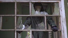 防毒面具的疯狂的潜随猎物者疯子从一个被破坏的房子看并且要攻击 股票录像