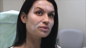 防皱做法:美丽的深色的女孩等待奶油的作用对她的面孔 影视素材