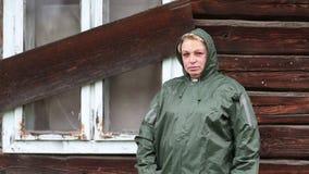 防水雨衣的妇女在无人居住的房子附近站立 股票录像