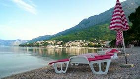 阳伞和懒人在空的海滩与镇和山在背景 股票录像