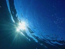 阳光光芒通过海洋 免版税库存图片