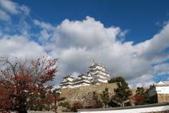 阳光和红色的白姬路城在树留给秋天蓝天背景 免版税库存照片