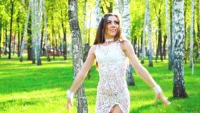 阳光在美女的性感的服装跳舞的在绿色公园 股票视频