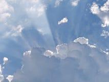 阳光打破在一朵蓬松白色云彩的边缘之间在蓝天的 库存图片
