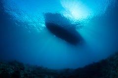 阳光现出轮廓的小船 免版税图库摄影