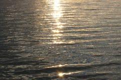 阳光的反射在水的在日落 免版税库存照片