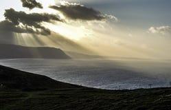 阳光通过云彩和在兰迪德诺,威尔士,英国附近的海 免版税图库摄影
