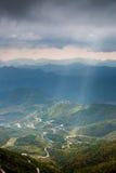 阳光通过点燃五颜六色的森林的云彩之间的空白 图库摄影