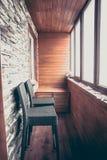 阳台用木板条和石头在葡萄酒船舶样式的小屋内部装饰的与大窗户栏柜台和酒吧椅子 免版税图库摄影