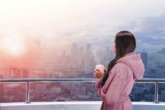 阳台的妇女享受城市视图的 图库摄影