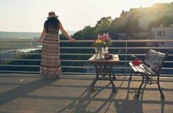 阳台的妇女日落的 图库摄影