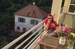 阳台的妇女日落的 免版税库存图片