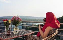 阳台的妇女日落的 免版税库存照片