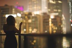 阳台的美丽的少妇有一杯的一件黑礼服的在夜城市的背景的酒 库存照片