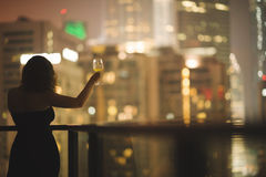 阳台的美丽的少妇有一杯的一件黑礼服的在夜城市的背景的酒 免版税图库摄影