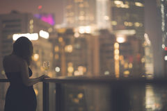 阳台的美丽的少妇有一杯的一件黑礼服的在夜城市的背景的酒 免版税库存图片