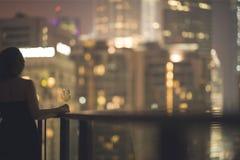 阳台的美丽的少妇有一杯的一件黑礼服的在夜城市的背景的酒 库存图片