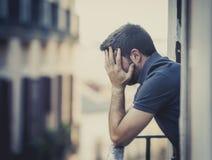 阳台的年轻人遭受情感危机的消沉的 免版税库存图片